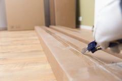 箱中取出纸板箱有建筑刀子的新的家具 搬到新房,新的家具购买  免版税库存图片