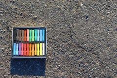 箱五颜六色的蜡笔,在沥青的白垩 库存图片