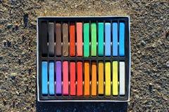 箱五颜六色的蜡笔,在沥青的白垩 免版税图库摄影