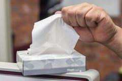 箱子与烙记的面巾纸组织在箱子用拔出一的手  免版税图库摄影