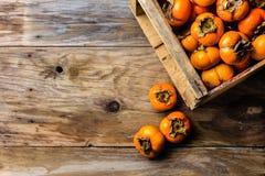 箱子新鲜水果在木背景的柿子亚洲柿树 复制空间 库存图片