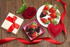 箱子用鲜美巧克力浸洗了草莓和玫瑰在桌上 日s华伦泰 免版税库存图片
