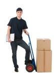 箱子移动。倾斜在推车的快乐的年轻送货员与 免版税库存照片