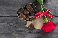 箱巧克力,在黑暗的背景的红色玫瑰 免版税库存图片