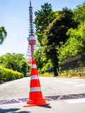 箱根,日本- 2017年7月02日:关闭在街道的橙色锥体有后边一个巨大的红色塔的,在箱根镇 库存图片