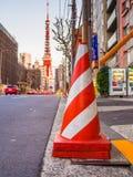 箱根,日本- 2017年7月02日:关闭在街道的橙色锥体有后边一个巨大的红色塔的,在箱根镇 免版税库存照片