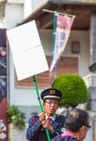 箱根,日本- 2017年11月5日:制服的一个人有在城市街道上的一个标志的 框架例证文本向量 垂直 免版税库存图片