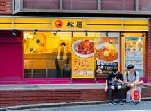 箱根,日本- 2017年7月02日:在等待的餐馆外面的未认出的人抽烟和位于区  库存照片