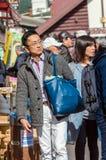 箱根,日本- 2017年11月5日:有一个蓝色袋子的一个人在城市街道上 垂直 图库摄影