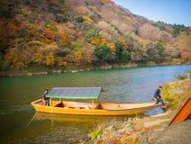 箱根,日本- 2017年7月02日:未认出在一条小船在有秋天风景,黄色,橙色和红色秋天的一个湖 库存图片