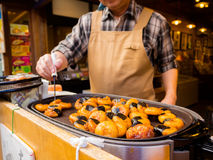 箱根,日本- 2017年7月02日:烹调食物的未认出的日本人在街道,根据流动食物在哪里站立 免版税库存照片