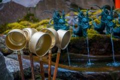 箱根,日本- 2017年7月02日:古铜色碗用对takle水的一根棍子与有一条古铜色龙的ablurred喷泉 免版税库存照片