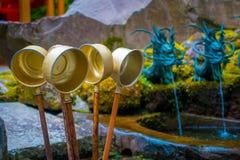 箱根,日本- 2017年7月02日:古铜色碗用对takle水的一根棍子与有一条古铜色龙的ablurred喷泉 库存图片