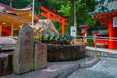 箱根,日本- 2017年7月02日:在一个岩石标志的Chinesse信件,与有一条古铜色龙的一个喷泉在日本 库存照片