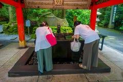箱根,日本- 2017年7月02日:未认出的在红色花托门输入的人民饮用水在Fushimi Inari寺庙的在京都, 免版税库存照片