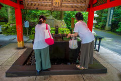 箱根,日本- 2017年7月02日:未认出的在红色花托门输入的人民饮用水在Fushimi Inari寺庙的在京都, 免版税库存图片