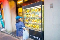 箱根,日本- 2017年7月02日:看食品店的未认出的妇女街道 库存照片