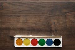 箱油漆和在桌上的一把刷子 库存图片