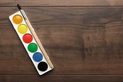 箱油漆和在桌上的一把刷子 免版税库存图片