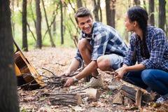 篝火的夫妇读书在森林里 库存照片