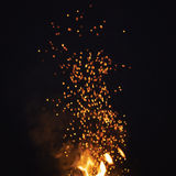 从篝火的火花夜有黑暗的背景 免版税库存照片