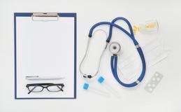 篡改与医学、听诊器和玻璃,顶视图的桌 库存照片