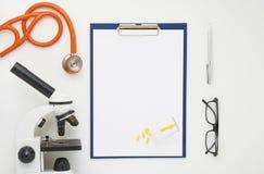 篡改与显微镜、听诊器和玻璃,顶视图的桌 免版税库存照片