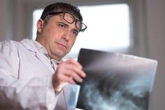 篡改佩带的一个白色实验室外套审查的X-射线图象 图库摄影