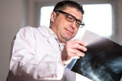 篡改佩带的一个白色实验室外套审查的X-射线图象 库存图片