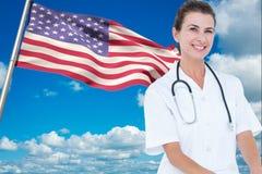 篡改佩带的白色外套和听诊器在美国国旗前面反对天空背景 免版税库存照片