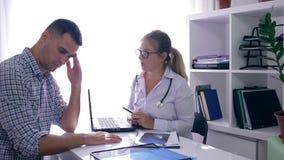 篡改坐在与膝上型计算机的桌上和X-射线、谈话坏消息然后支持的患者在医疗办公室 影视素材