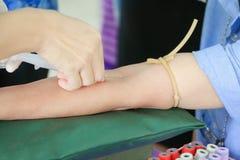 篡改射入在胳膊的针注射器收集测试的血液健康 免版税库存照片