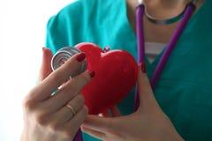篡改拿着心脏和听诊器在白色背景 免版税库存图片