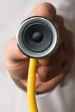 篡改拿着有一位报告人的一个听诊器在他的手上 库存照片