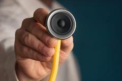 篡改拿着有一位报告人的一个听诊器在他的手上 免版税库存图片