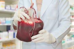 篡改拿着注入的,献血新鲜的血液袋子 库存图片