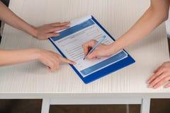 篡改指向签医疗合同的文件和患者 免版税图库摄影