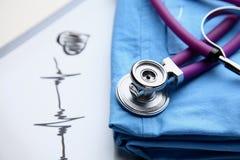 篡改有医疗听诊器的外套在书桌上 免版税库存照片