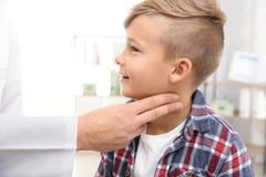 篡改检查小男孩的脉冲与手指 免版税库存照片