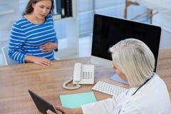 篡改谈论与在数字式片剂的怀孕的患者 免版税库存图片