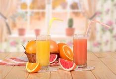 篮子柑桔,杯桔子和葡萄柚汁和 免版税库存图片