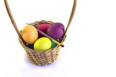篮子用五颜六色的在wh隔绝的复活节彩蛋和油漆刷 免版税库存照片