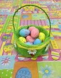 篮子用五颜六色的复活节彩蛋在五颜六色的桌上 库存图片
