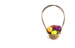 篮子用五颜六色的被隔绝的复活节彩蛋和油漆刷 库存图片