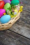 篮子用五颜六色的鸡蛋和春天在木桌上开花 库存图片