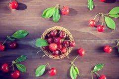 篮子用在一张木桌上的一棵樱桃在一个绿色庭院的背景 库存照片