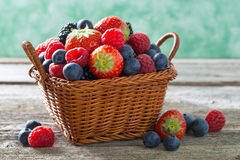 篮子用在一张木桌上的新鲜的水多的莓果,水平 免版税库存图片