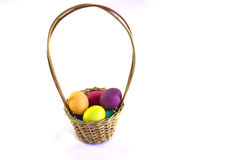 篮子用在白色背景的五颜六色的复活节彩蛋 免版税库存图片