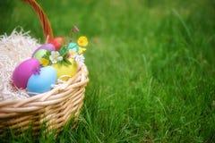 篮子用在绿色春天草的五颜六色的复活节彩蛋 免版税图库摄影