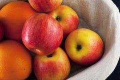 篮子用苹果和桔子在蓝色背景 免版税库存图片